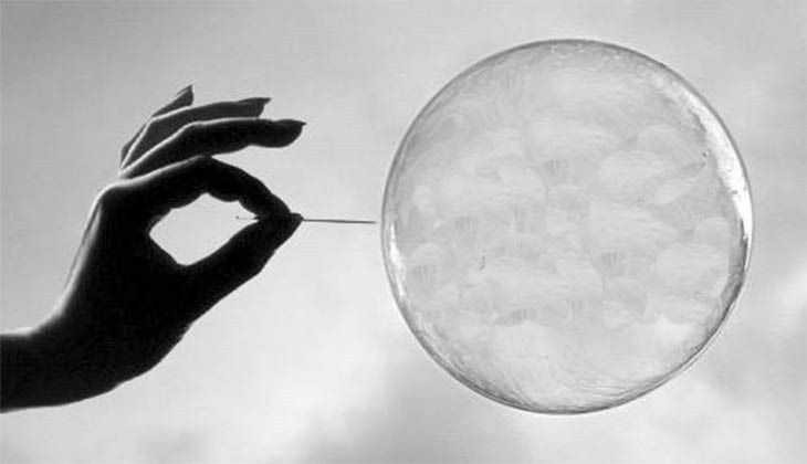 A person popping a bubble with a needle